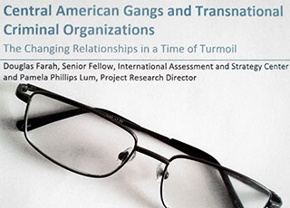 Reading glasses lying on a copy of Douglas Farah's publication Central American Gangs and Transnational Criminal Organizations